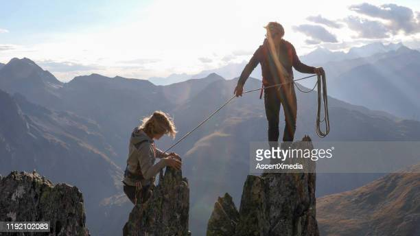 female mountaineer scrambles up mountain ridge - simple living stock pictures, royalty-free photos & images
