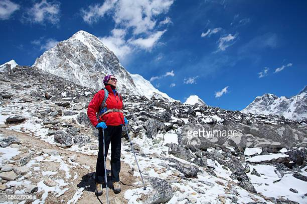 Female mountaineer standing alone on the mountain and looking aw