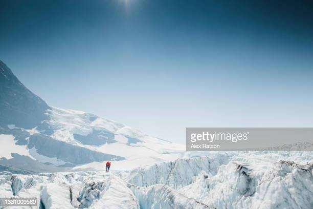 female mountaineer walks between multiple deep crevasses on a rugged glacier - between stock pictures, royalty-free photos & images