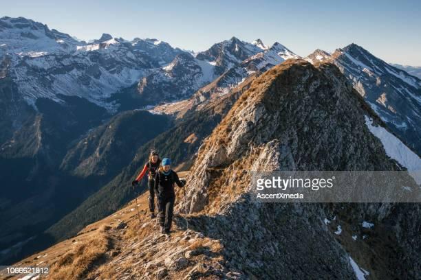 vrouwelijke bergbeklimmers bewegen op de heuvelrug - zwitserland stockfoto's en -beelden