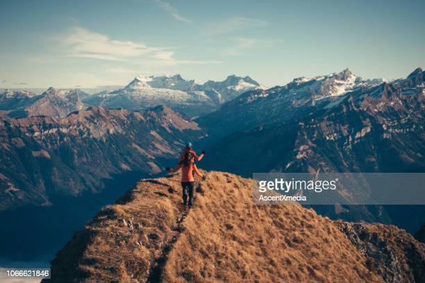 female mountaineers moving up mountain ridge - mountain ridge stock pictures, royalty-free photos & images