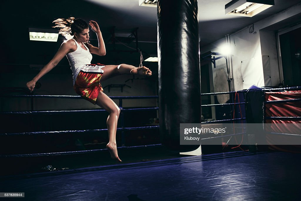Female muay thai fighter training with a punching bag : Stock Photo