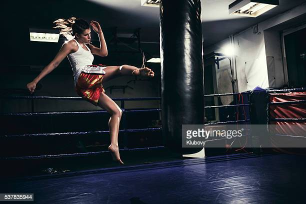 female muay thai fighter training with a punching bag - muay thai stock pictures, royalty-free photos & images
