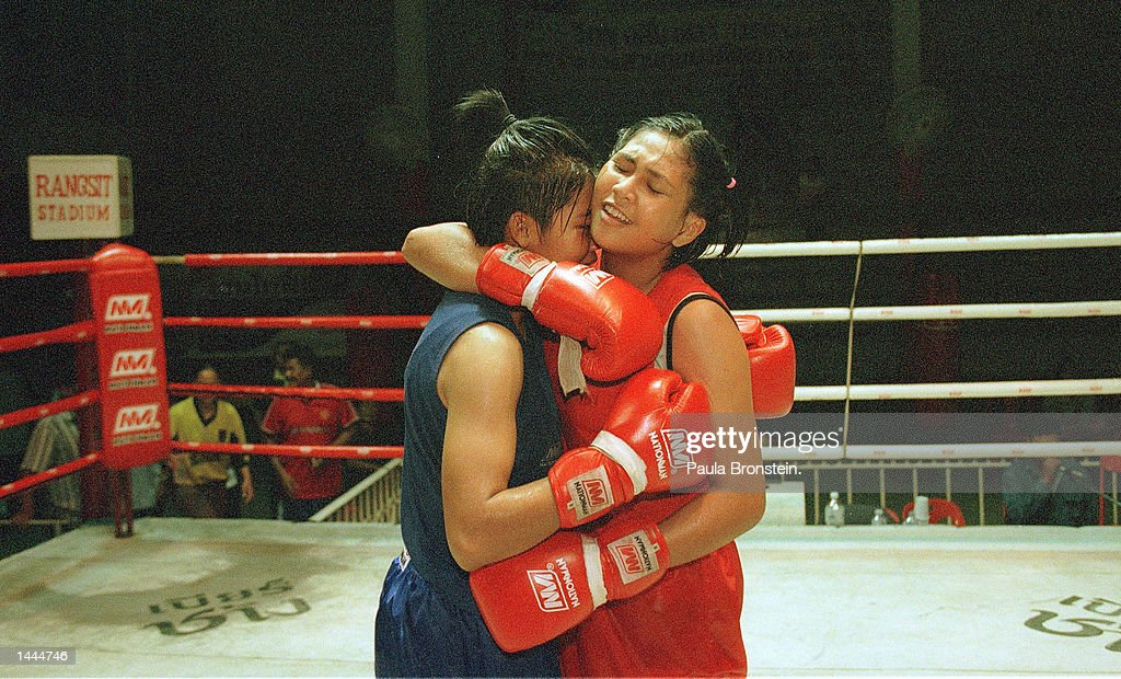 Female Muay Thai fighters hug each other in mutual respect after a recent fight at Rangsit stadium May, 2000 in Bangkok, Thailand.