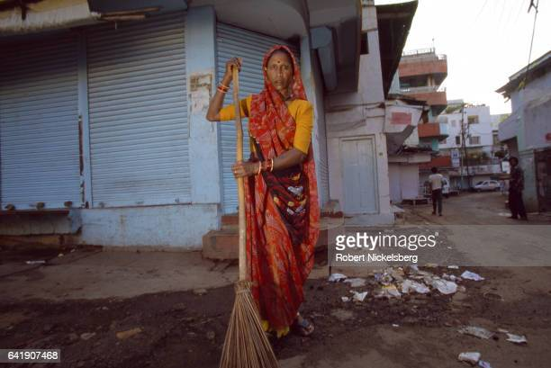 A female municipal worker and member of the Dalit caste sweeps the streets October 1 1997 in Bhopal India She earns about 1000 INR per month cleaning...
