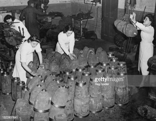 Female munitions workers arrange component parts for 500lb general purpose bombs for use with the Royal Air Force at a munitions production assembly...