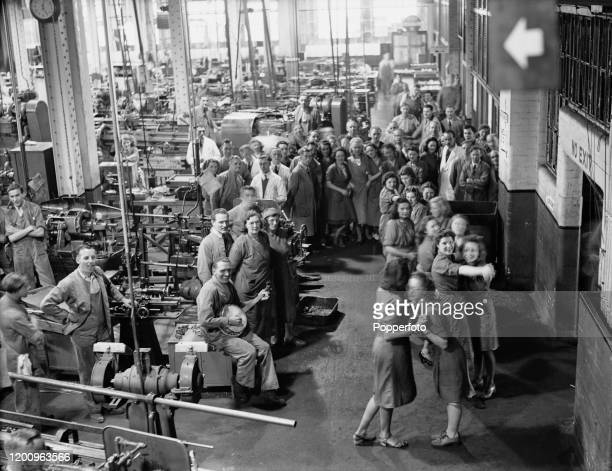 Female munitions workers dance together as a male colleague plays a banjo during a break in production in the machine shop of a munitions factory in...