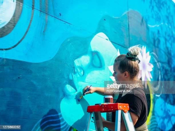 artiste féminin de peinture murale au travail - peinture murale photos et images de collection
