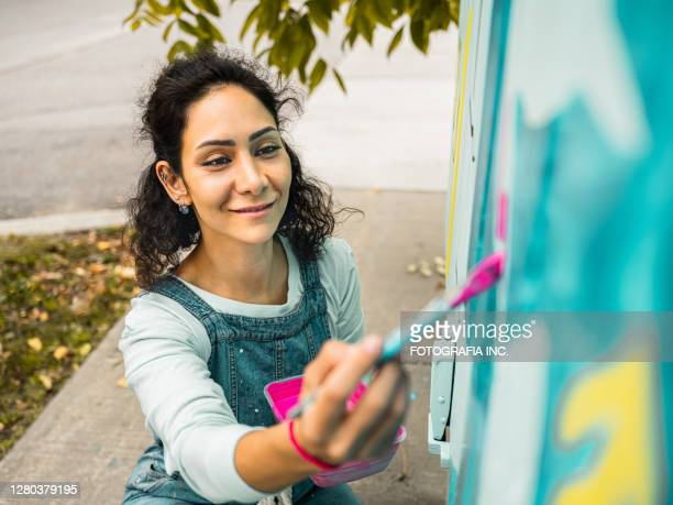 female mural artist at work - artist stock pictures, royalty-free photos & images