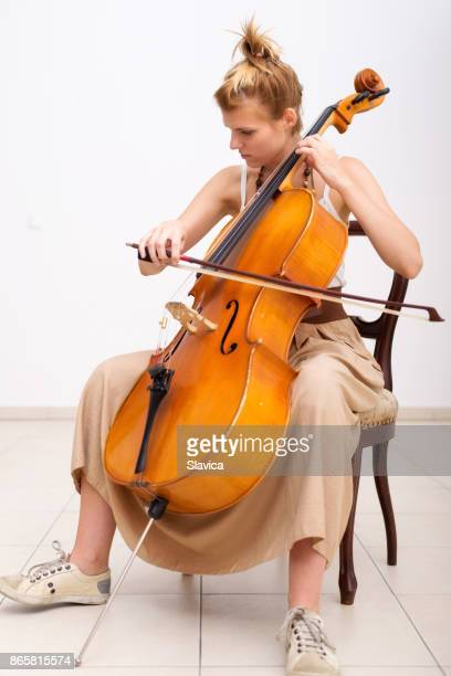 female musician playing cello at home - cello stock pictures, royalty-free photos & images