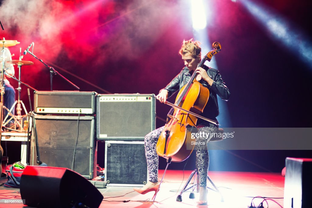 Female musician playing cello on stage under spotlights : Stock Photo