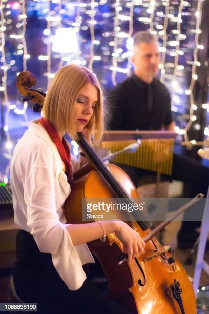 Female musician playing cello with her band on the concert