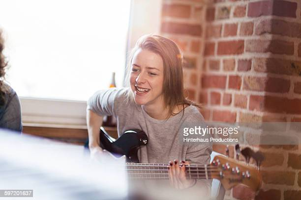 female musician playing guitar - plucking an instrument stock pictures, royalty-free photos & images