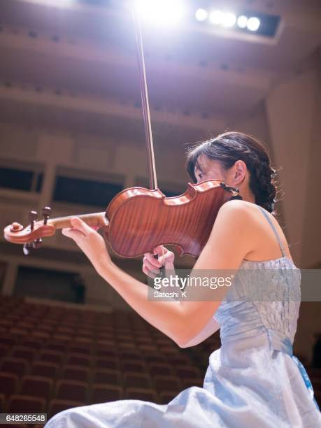 Female musician playing violin on concert stage
