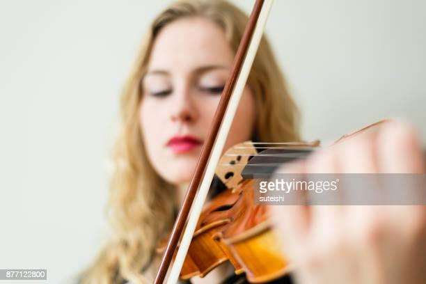 weibliche musiker spielen violine - musikinstrument stock-fotos und bilder