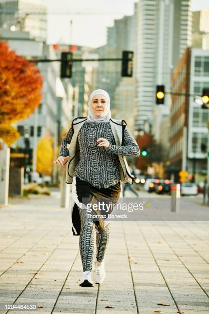 female muslim athlete running in city on fall afternoon - scarf stock pictures, royalty-free photos & images