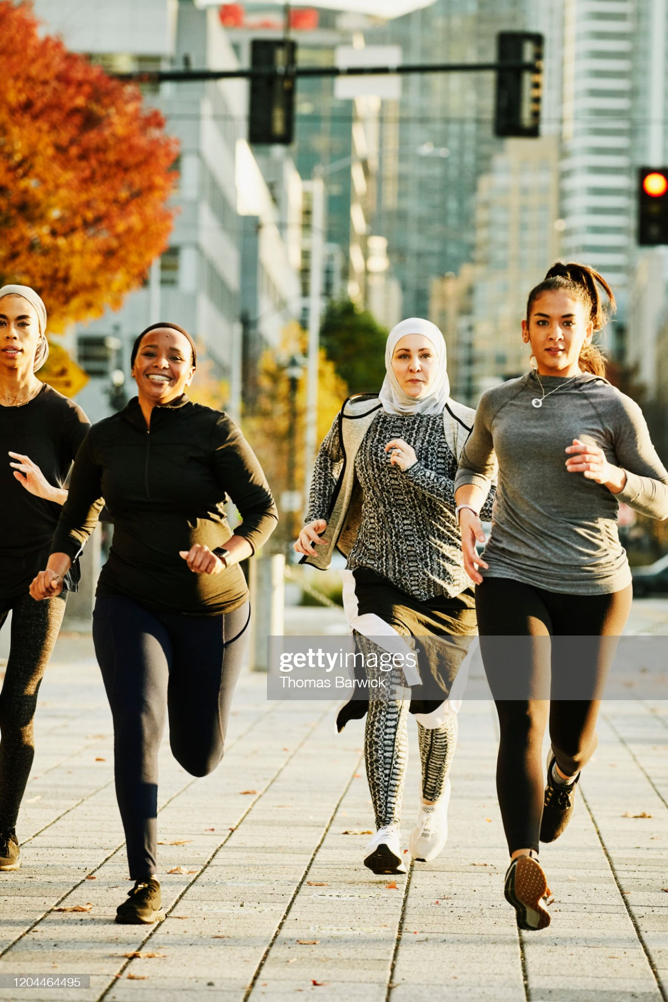 Female Muslim athletes running in city on fall afternoon : Stock Photo