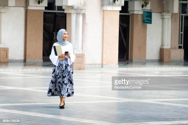 female muslim college student walking on campus full length - malaysian culture stock pictures, royalty-free photos & images