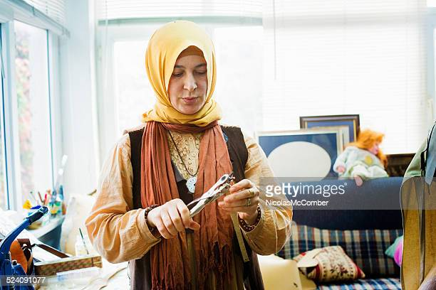 Weibliche muslimische Leder artisan punching Löcher in Leder strip