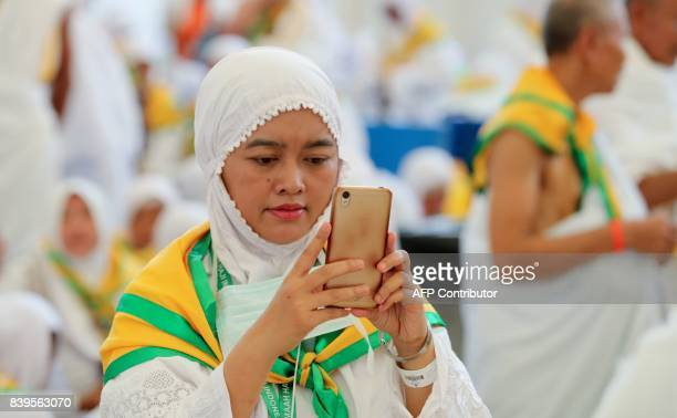 A female Muslim pilgrim uses her cell phone upon arrival at Jeddah airport on August 26 prior to the start of the annual Hajj pilgrimage in the holy...