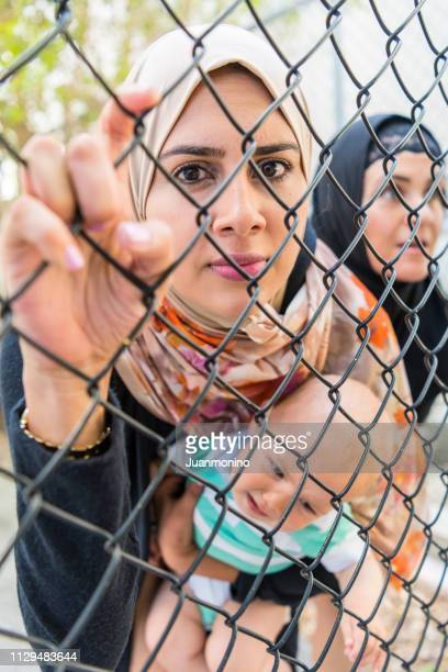 female muslim refugee holding her baby watching through a fence - refugee camp stock pictures, royalty-free photos & images