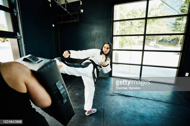 Female Muslim self defense instructor demonstrating kick during class in gym