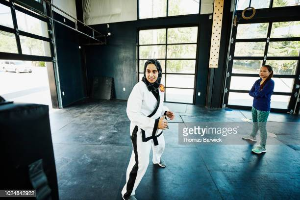 Female Muslim self defense instructor preparing to demonstrate kick during class in gym