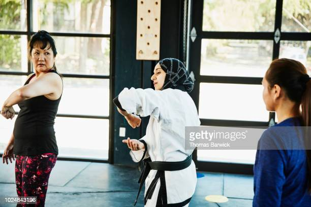Female Muslim self defense instructor showing students technique during class in gym