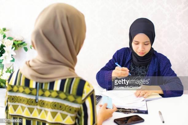 領収書を記入女性イスラム教徒店主 - レシピ帳 ストックフォトと画像