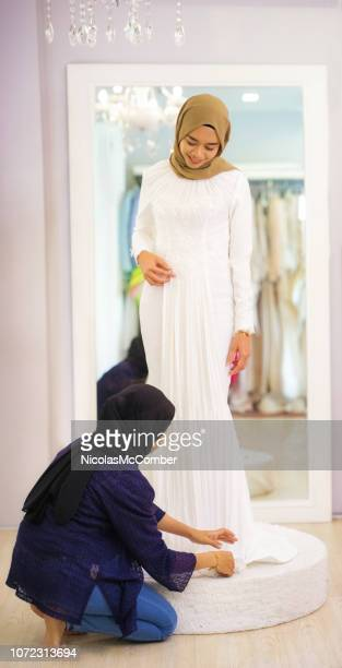 Female Muslim tailor places finishing touches on wedding dress hem