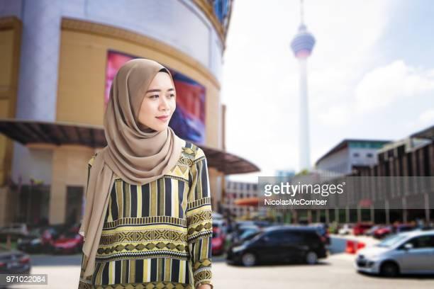 female muslim young adult walking downtown kuala lumpur - menara kuala lumpur tower stock photos and pictures