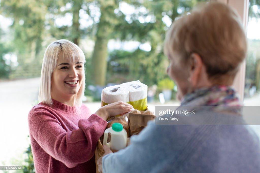 Female Neighbor Helping Senior Woman With Shopping : Stock Photo
