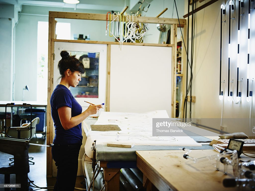 Female neon artist working on smart phone in loft : Stock Photo