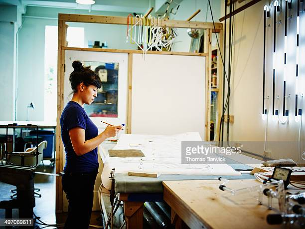 female neon artist working on smart phone in loft - accessibility stock pictures, royalty-free photos & images