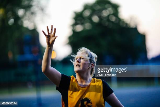 female netball player having just thrown the ball on outdoor sports court at dusk