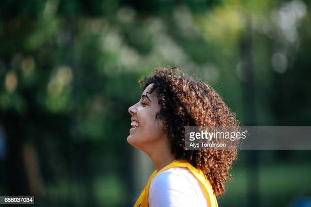 female netball player smiling on court in urban park
