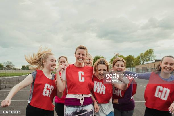 female netball team celebrating a win! - sports team stock pictures, royalty-free photos & images