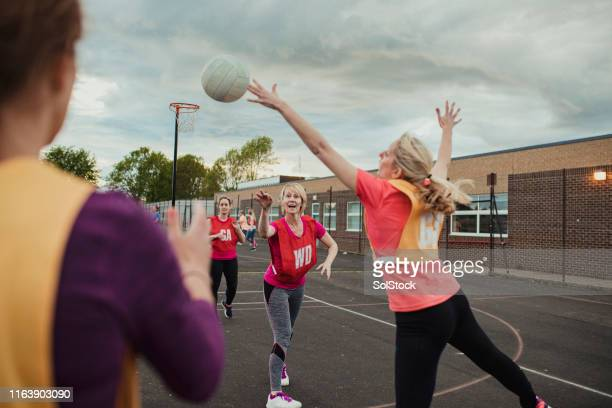 female netball team enjoying the game! - team sport stock pictures, royalty-free photos & images