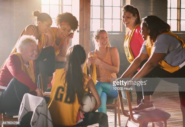 female netball team members sitting and laughing in gym. - girl power provérbio em inglês - fotografias e filmes do acervo