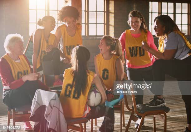 Female netball team members sitting and laughing in gym.
