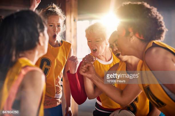 female netball team preparing to training in gym. - sportmannschaft stock-fotos und bilder