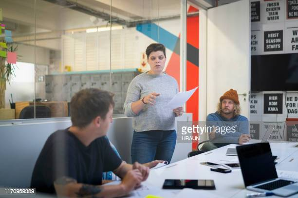 female newspaper editor discussing with colleagues - press conference stock pictures, royalty-free photos & images