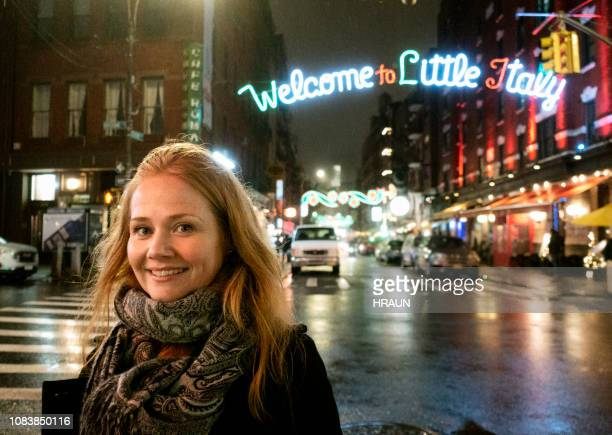 female next to  mulberry street in nyc. - little italy new york foto e immagini stock