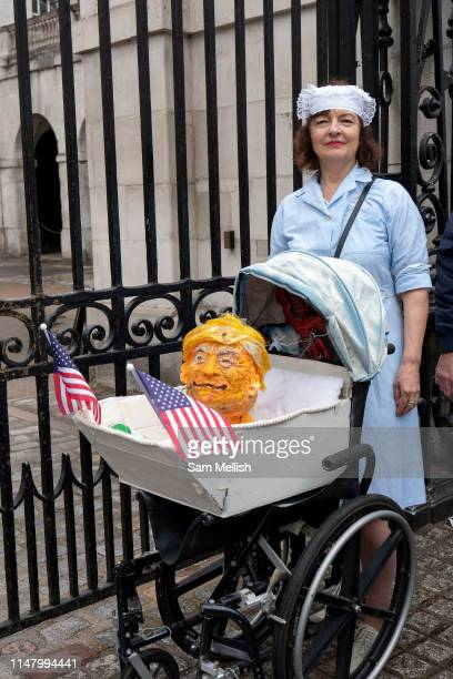 A female NHS nurse with a mock pram and fake Donald Trump head during a demonstration against US President Donald Trump's state visit to the UK on...