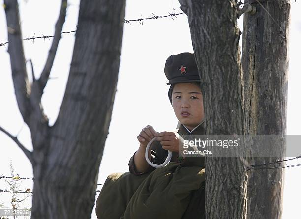 A female North Korean soldier stands guard on the banks of the Yalu River opposite the Chinese border city of Dandong October 11 2006 in Uiju...
