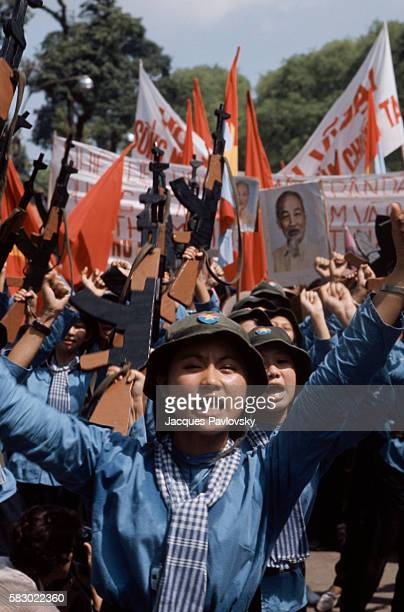 Female North Vietnamese troops enter Saigon carrying wooden rifles red flags and portrait of Ho Chi Minh