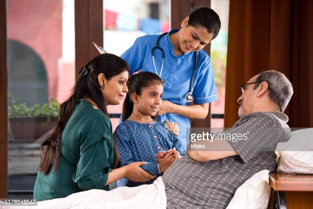 female nurse and family with senior patient at home - visit stock pictures, royalty-free photos & images