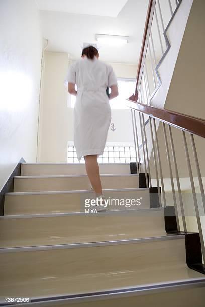 Female nurse ascending staircases