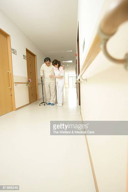 Female nurse assisting patient with walking cane