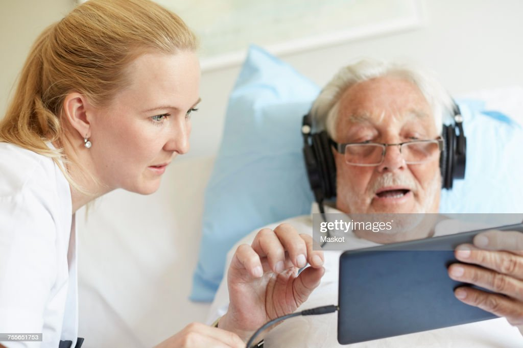 Female nurse assisting senior man in using digital tablet on hospital bed : Stock Photo
